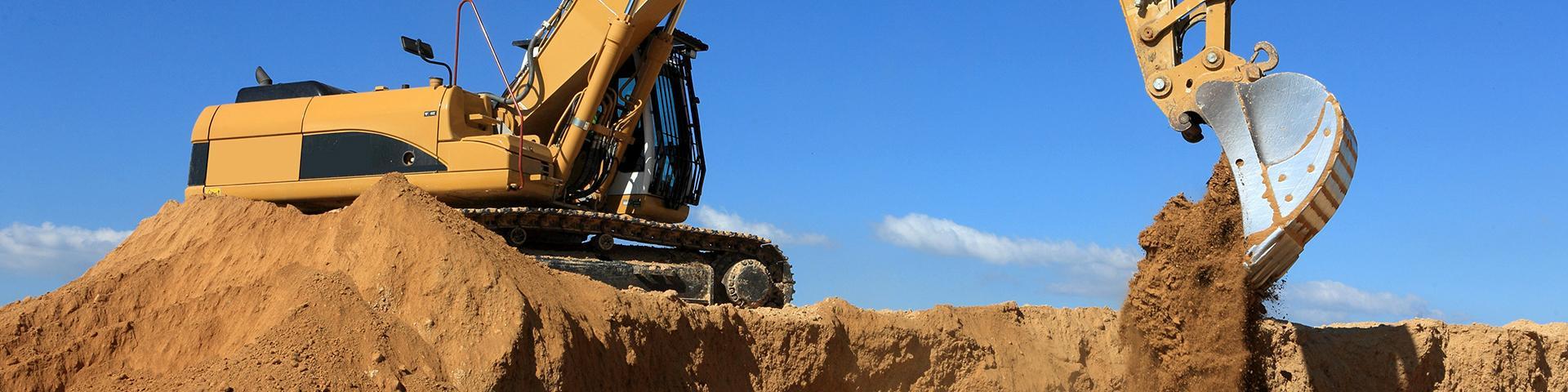 Vue d'un engin de chantier déversant de la terre